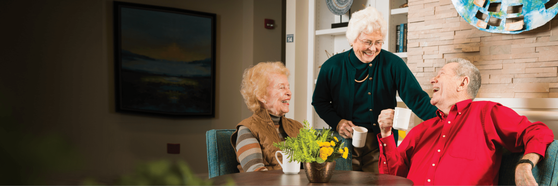 Three Bethany Village residents smile and enjoy coffee